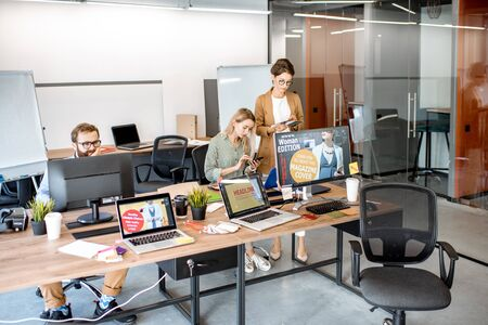 Modern office room of web designers with working places and people working 写真素材