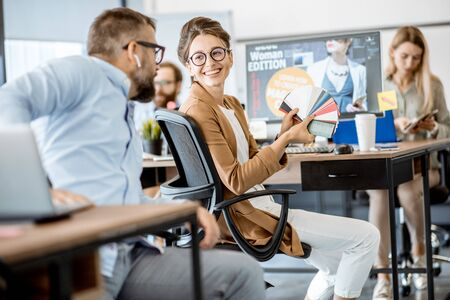 Group of creative and happy coworkers working on web design with computers in the office