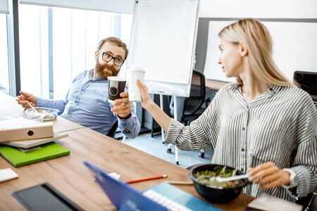 Man and woman eating salad and drinking coffee during a lunch time on the working place without leaving the office