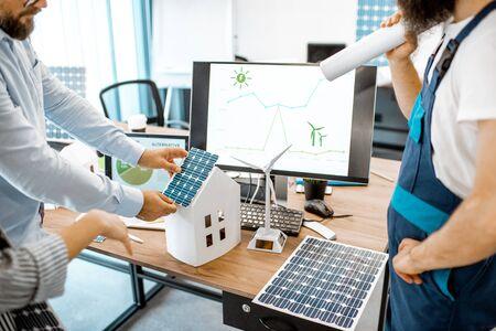 Personas que trabajan en un proyecto de energía alternativa, trabajando con modelo de casa y computadora en la oficina, primer plano en el lugar de trabajo