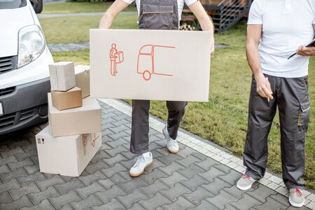 Delivery men moving cardboard boxes outdoors, delivering goods with cargo vehicle, close-up on boxes with no face Stock Photo