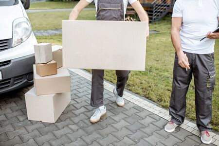 Delivery men moving cardboard boxes outdoors, delivering goods with cargo vehicle, close-up on boxes with blank space