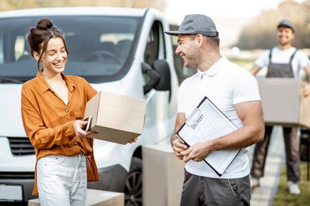 Courier with checklist delivering goods to a young woman by cargo van vehicle, mover with cardboard parcels on the background 写真素材