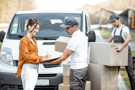 Courier delivering goods to a young woman by cargo van vehicle, client signing documents, mover with cardboard parcels on the background 写真素材
