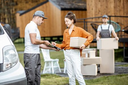 Couriers delivering goods to a young woman home by cargo van vehicle, client signing documents, mover with cardboard parcels on the background