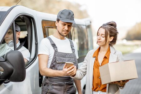 Delivery company employees in uniform delivering goods to a client by cargo van vehicle, woman signing on a smartphone, receiving parcel outdoors