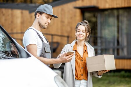 Delivery company employees in uniform delivering goods to a client by car, woman signing on a smartphone while receiving parcel near home