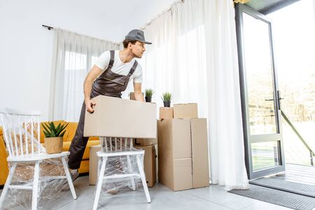 Handsome mover in workwear performing professional delivery of a goods and furniture during relocation process to a new house, interior view Stock fotó