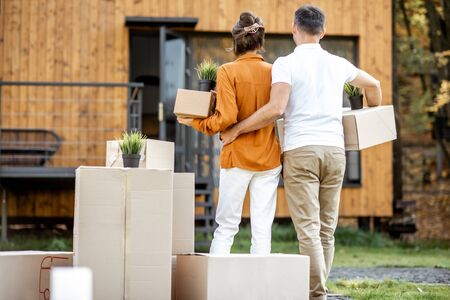 Young couple standing back with cardboard boxes in front of their new house. Concept of a relocation into a new home
