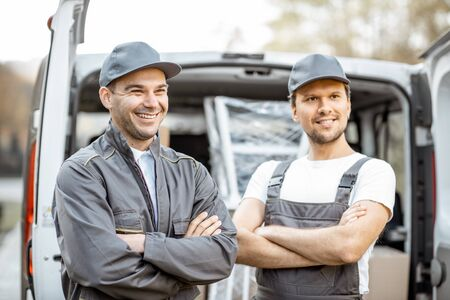 Portrait of a two cheerful delivery men or movers in workwear standing near a cargo vehicle trunk full of boxes to deliver