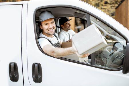 Employés joyeux de l'entreprise de livraison livrant des marchandises aux clients sur un véhicule cargo, beau courrier regardant par la fenêtre de la voiture avec un colis Banque d'images