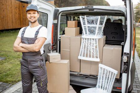 Ritratto di un bell'uomo delle consegne in uniforme in piedi vicino a un bagagliaio di un furgone pieno di scatole e mobili durante un trasloco