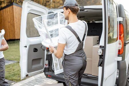 Delivery company employees unloading cargo van vehicle, delivering some goods and furniture to a clients home. Relocation and professional delivery concept
