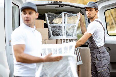 Employés d'une entreprise de livraison déchargeant un véhicule de transport de marchandises, livrant des marchandises et des meubles au domicile d'un client. Concept de relocalisation et de livraison professionnelle Banque d'images