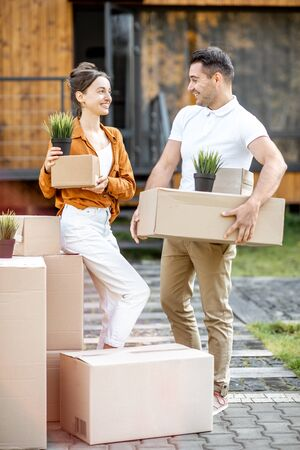 Portrait of a happy young couple standing with cardboard boxes in front of their new house. Concept of a relocation into a new home