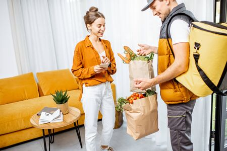 Courier in uniform with thermal bag delivering fresh groceries in paper bags to a client home. Woman with smartphone checking her order Stock fotó
