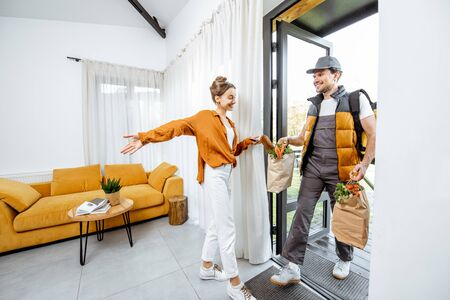 Courier in uniform delivering fresh groceries home for a young client, wide interior view. Online shopping and home delivery concept