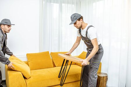 Professional movers in uniform placing furniture at the living room of a new apartment during a relocation process