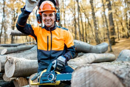 Portrait of a cheerful professional lumberjack in protective workwear standing with a chainsaw on a pile of logs in the forest Stock fotó