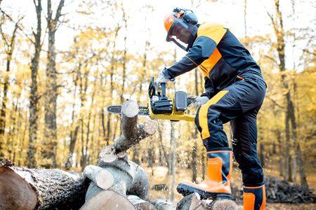 Bûcheron professionnel en vêtements de travail protecteurs travaillant avec une tronçonneuse dans la forêt. Le bûcheron fait une exploitation forestière à l'extérieur