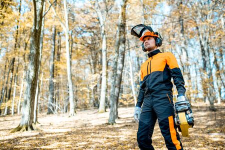 Lifestyle portrait of a professional lumberjack in protective workwear walking with a chainsaw in the forest