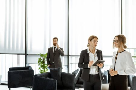 White-collar employees of financial institution or other big copany having some business, standing and talking in the luxury office