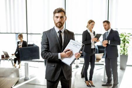 Portrait of a bank employee with home loan agreement standing at the bank office with coworkers on the background