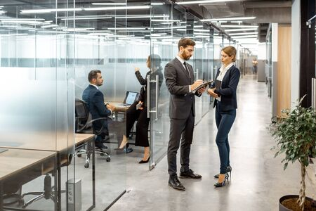 Business people talking in the hallway of the modern office building with employees working behind glass partitions. Work in a large business corporation Foto de archivo