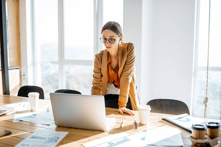 Young woman dressed casually in the suit working with laptop at the large meeting table in the sunny office room