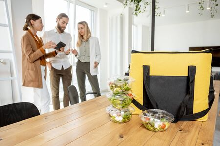 Office workers standing in the office with business lunches and delivery bag on the foreground. Concept of takeaway healthy food delivery to the work