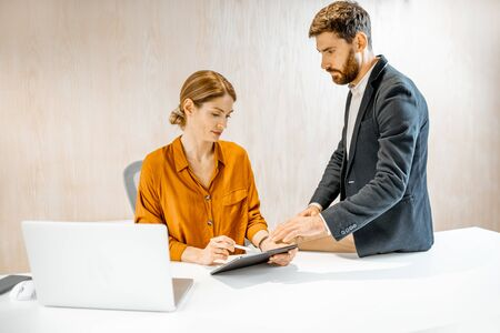 Businessman having some informal conversation with work colleague or woman boss in the office Stock fotó