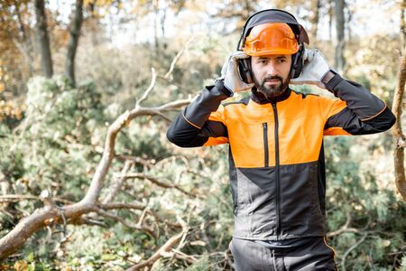 Waist-up portrait of a professional lumberman wearing protective clothes, preparing for logging work in the pine forest Banque d'images