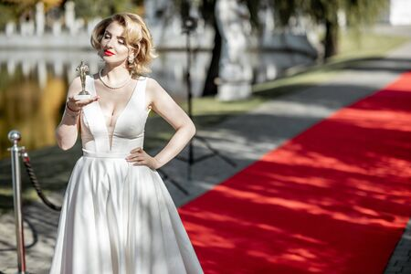 Portrait of a beautiful woman in white dress as a well-known actress holding famous movie award on the red carpet outdoors
