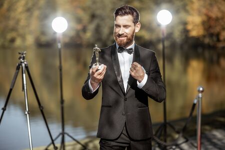 Portrait of a happy man strictly dressed in tuxedo as a well-known actor excited with famous award statue during the ceremony outdoors