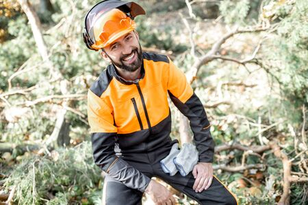 Portrait of a cheerful lumberman in protective workwear resting after the hard work in the forest