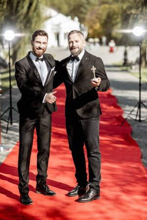 Two elegant men strictly dressed in suits as a well-known film actors having fun during awards ceremony on the red carpet outdoors