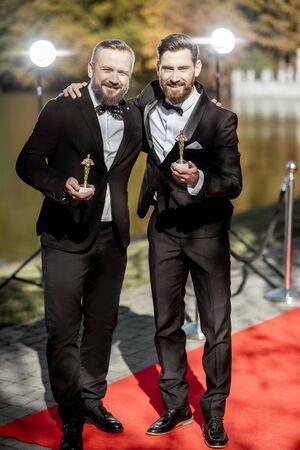 Porträt von zwei eleganten Männern, die während der Preisverleihung auf dem roten Teppich im Freien streng in Anzügen als bekannter Filmschauspieler gekleidet sind