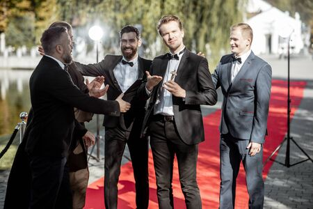 Men as a famous movie actors gathering together and greeting each other on the red carpet at the awards ceremony outdoors