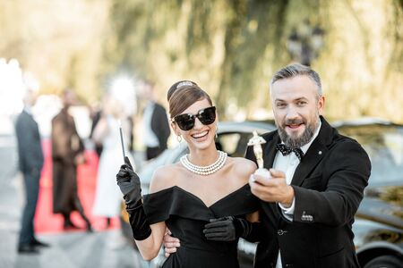 Elegant man and woman as a famous movie actors walking together and having fun during awards ceremony outdoors