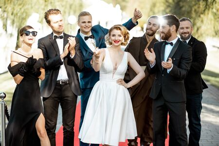 Group portrait of a famous movie actors standing together on the red carpet during awards ceremony outdoors