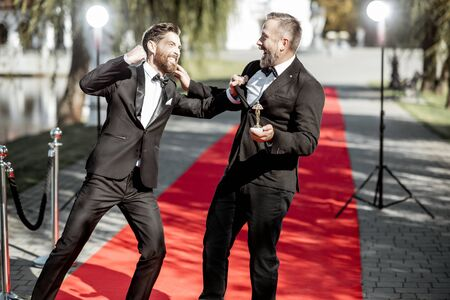 Funny portrait of a two men strictly dressed as a film actors fighting on the red carpet during awards ceremony outdoors