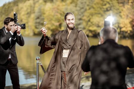 Mann im Kostüm als bekannte Filmfigur, der während der Preisverleihung mit nervigen Fotoreportern über den roten Teppich spaziert