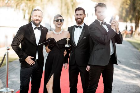 Group portrait of an elegant people as a famous movie actors standing together on the red carpet during awards ceremony outdoors