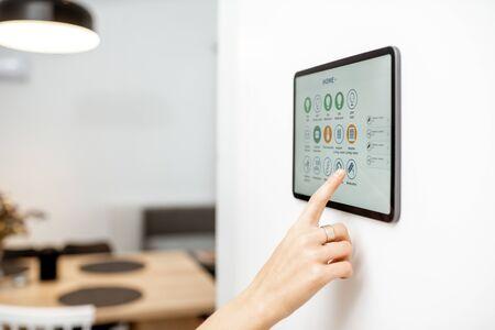 Control de la casa con un panel de pantalla táctil digital instalado en la pared. Primer plano en una pantalla con aplicación móvil para la gestión de dispositivos inteligentes Foto de archivo