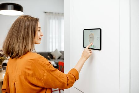 Young woman controlling temperature in the living room with a digital touch screen panel installed on the wall. Concept of heating control in a smart home Imagens
