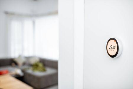 Termostato inteligente redondo con pantalla táctil instalado en la pared en interiores. Concepto de regulación de calefacción doméstica inteligente. Ver con espacio de copia Foto de archivo