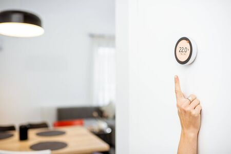 Round smart thermostat with touch screen installed on the wall with a hand trying to reach it. Smart home heating regulation concept