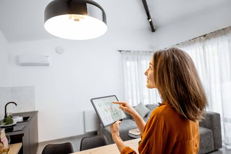 Young woman controlling home light with a digital tablet in the living room. Concept of a smart home and light control with mobile devices