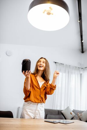 Happy woman controlling home light with a smart speaker in the living room. Concept of a smart home and light control with voice command Stock fotó