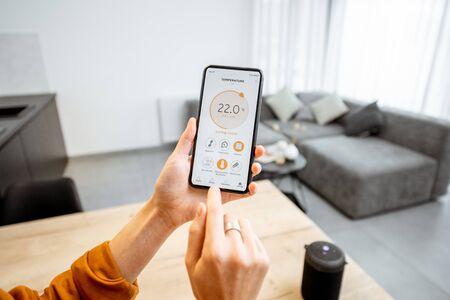 Controlar la temperatura de calefacción del hogar con una casa inteligente, primer plano en el teléfono. Concepto de hogar inteligente y aplicación móvil para administrar dispositivos inteligentes en el hogar Foto de archivo